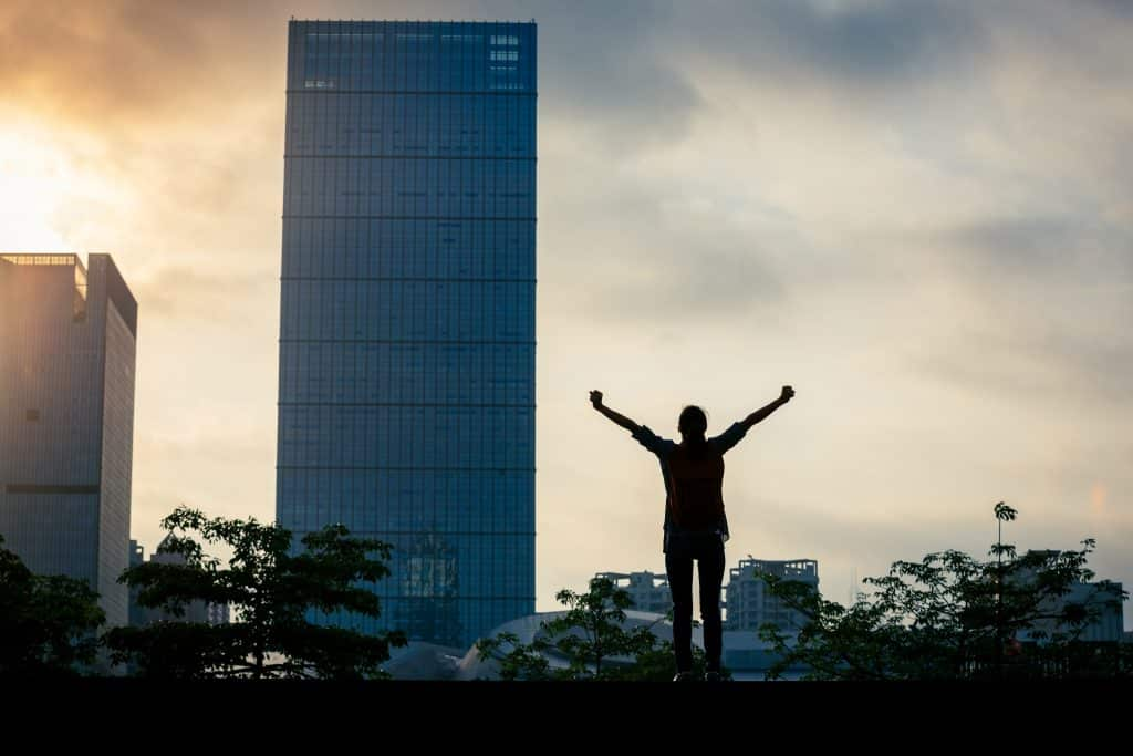 Young woman with self belief standing with arms open in city